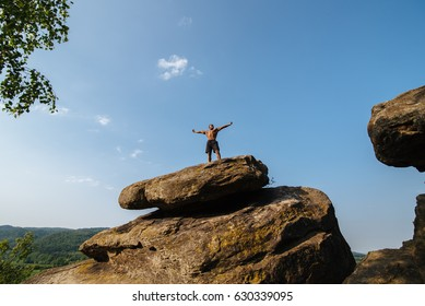 Black man athlete stands on a rock against the blue cloudy sky