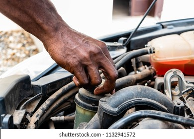 black man as Auto mechanic working in garage near car engine. Repair service and transport concept. Hands of African American car mechanic in auto repair service.