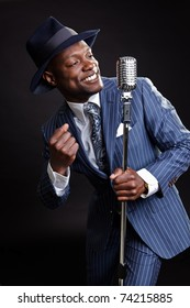 Black man with blue striped suit and blue hat singing.