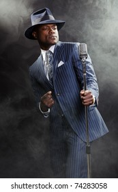 Black man with blue striped suit and blue hat singing. Smoky nightclub