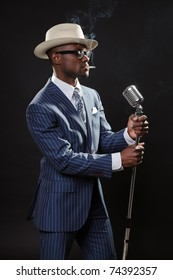 Black man with blue striped suit and blue hat singing in a smoky nightclub like a cotton club