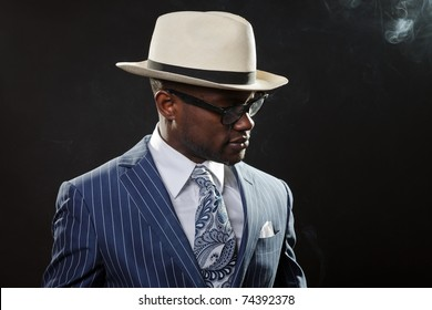 Black man with blue striped suit and hat