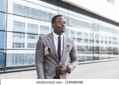 black man businessman in a business suit, expensive watch and glasses with a newspaper goes against the backdrop of a modern city to work