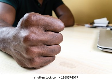 Black man with clenched fist on the desk. African man hitting pounding or slamming his fist on the wooden table for Angry Anger concept