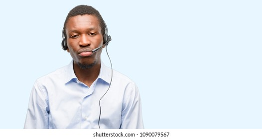 Black man consultant of call center with sleepy expression, being overworked and tired