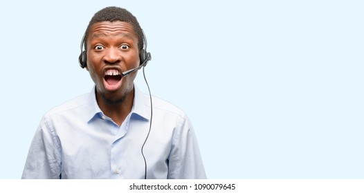 Black man consultant of call center stressful, terrified in panic, shouting exasperated and frustrated. Unpleasant gesture. Annoying work drives me crazy