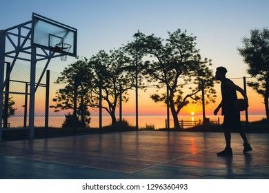 black man doing sports, playing basketball on sunrise, silhouette