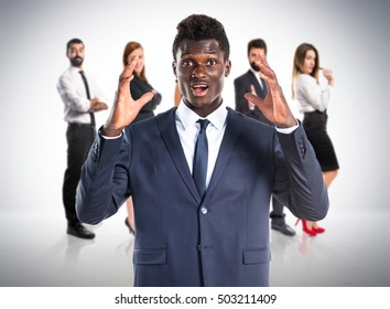 Black man doing surprise gesture with many people behind