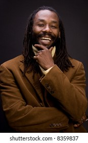 A black man with dreadlock hair isolated on a black background.