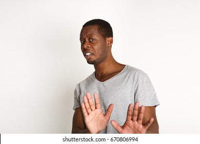 Black man expressing disgust on face, grimacing on white studio background. Negative emotions