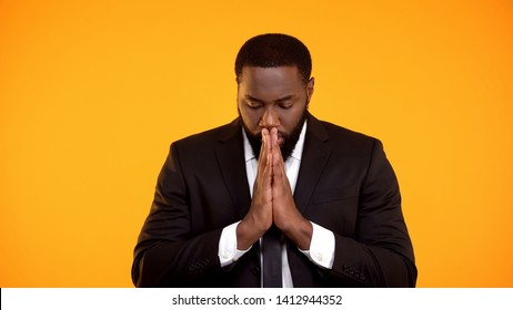Black man in formal suit praying for successful negotiations important interview