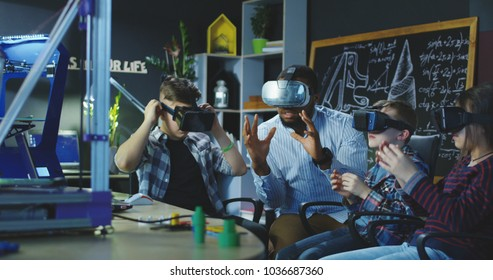 Black man with group of kids having lesson about 3d modeling wearing VR glasses in lab.