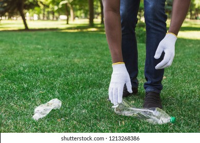 Black man hand picking up plastic bottle for recycling, ecology and volunteering concept, copy space