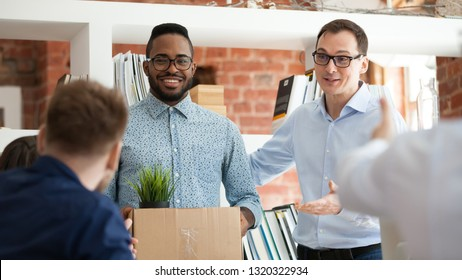Black man having first working day getting acquainted with colleagues standing in office in front of workmates. Boss introducing employee, newcomer holds box with belongings starting career in company