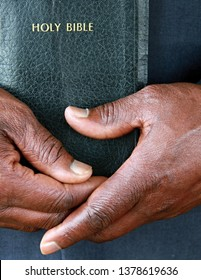 black man holding the Holy Bible after praying at a service in church stock image and stock photo
