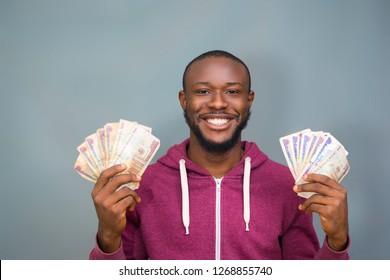 Black man holding money on both hands smiling