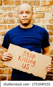 """A black man is holding a sign that says """"Stop killing us"""" in protest to police brutality"""