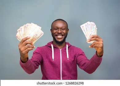 Black man holding some money on both hands happy