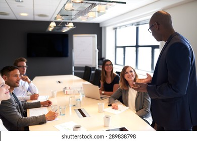 Black man leading a meeting with a group of executives in a conference room