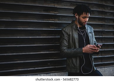 Black man listen music on street. Horizontal outdoor shoot with copy space