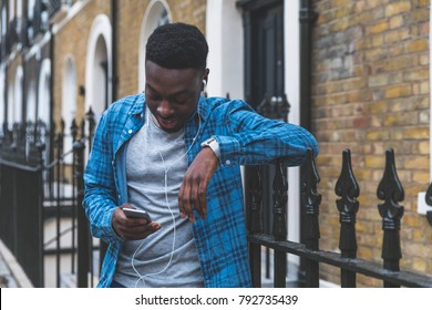 Black man listening music with phone in London. Young man wearing a checked shirt, holding a smart phone and wearing white earphones. Lifestyle and relax concepts