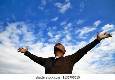 black man praying to god with arms outstretched looking up to the sky stock photo