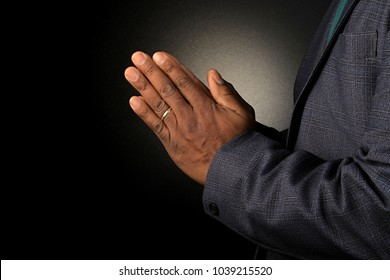 black man praying hand with black background stock image and stock photo