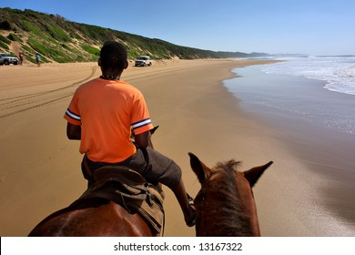 Black man rides a horse on beach. Shot in Sodwana Bay Nature Reserve, KwaZulu-Natal province, Southern Mozambique area, South Africa.