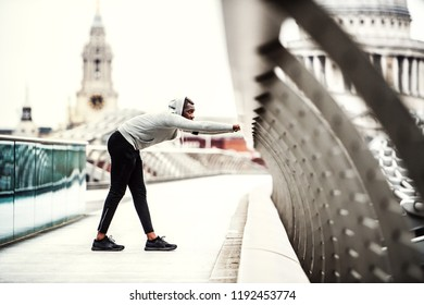 Black man runner on the bridge in a city, stretching. - Shutterstock ID 1192453774