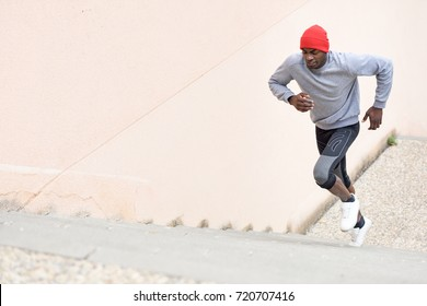 Black man running upstairs outdoors. Young male exercising with city scape at the background.