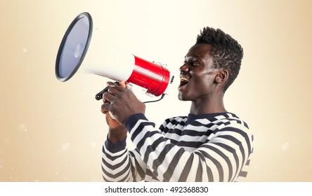 Black man shouting by megaphone over ocher background
