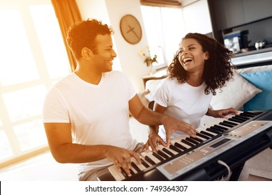 A black man sits in the living room of his apartment and plays a synthesizer. Next to him sits his girlfriend and plays with him. They like to play music together.
