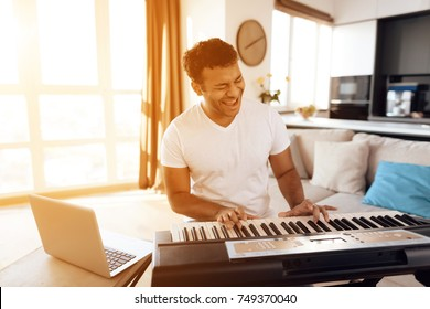 A black man sits in the living room of his apartment and plays a synthesizer. He composes music. Nearby is a gray laptop. A man likes to play music.