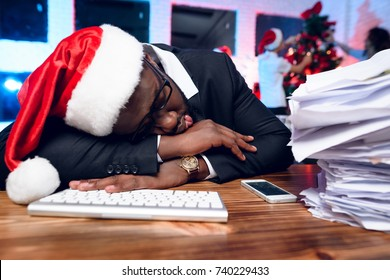 A black man is sitting at his desk on New Year's Eve. He has a lot of work and he fell asleep at the table. Behind him, colleagues decorate the New Year tree. He wears a Christmas hat.