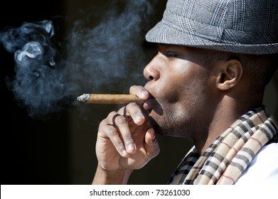 Black man smoking cigar portrait with hat.