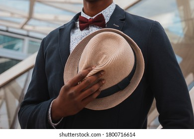Black man in suit and bowtie holding hat on chest
