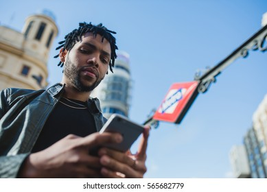 Black man using phone in front of a subway station. Horizontal shoot outdoors