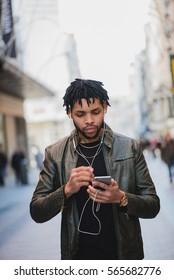 Black man walking and listen music on street. vertical outdoor shoot