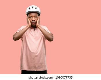 Black man wearing bike helmet covering ears ignoring annoying loud noise, plugs ears to avoid hearing sound. Noisy music is a problem.