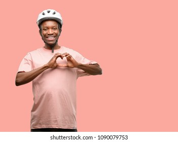 Black man wearing bike helmet happy showing love with hands in heart shape expressing healthy and marriage symbol