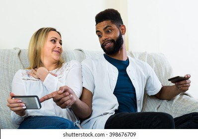 Black man and white woman 25s sitting on sofa with mobiles