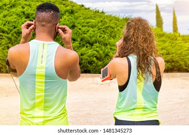 Black man and white woman runners and athletes with a healthy lifestyle put the music headphones in their ears to start the race and carry the arm attached to their smartphones