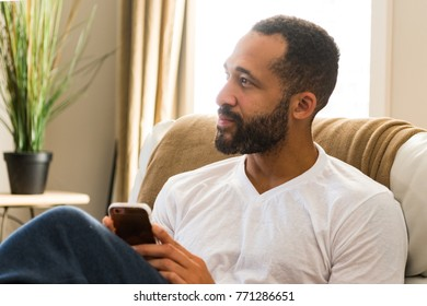 Black man working on his cell phone at home