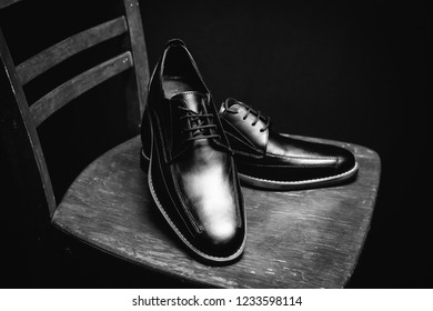 Black man's shoes on wooden chair