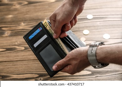 Black man's wallet in man hands pulling out a banknote over dark wooden background