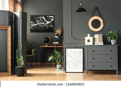 Black map on grey wall in dark living room interior with plants and poster. Real photo