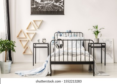 Black map on white wall of fashionable kid's bedroom with industrial single bed and nightstand with clock and cup