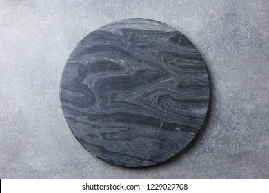 Black marble texture board on grey background. Top view. Copy space.
