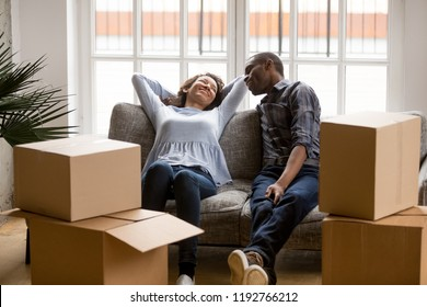 Black married couple sitting on couch in living room at house. Smiling happy wife and husband relaxing resting unopened belongings still in their cardboard boxes. Moving and relocate new home concept
