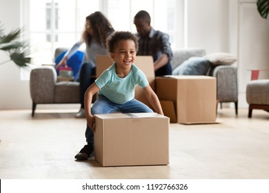 Black married couple sitting on couch in living room unpacking boxes with belongings at new home. Little funny African boy carrying playing with cardboard box. New home, relocation and moving concept